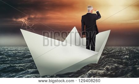 Rear view of mature businessman looking away against paper boat floating on the sea