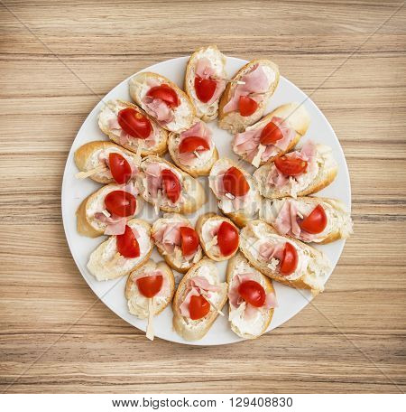 Tasty canapes with butter ham and cherry tomatoes. Full white plate. Food theme. Refreshments for guests. Catering theme.