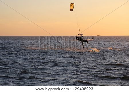 Kite surfing with an orange vibrant sunset