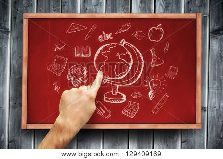 Hand pointing against blackboard with copy space on wooden board