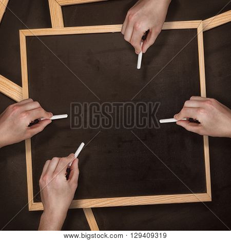 Multiple hands writing with chalk against blackboard with copy space