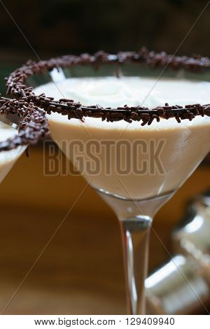 Chocolate martini garnished with chocolate powder and sprinkles on the rim and whip cream
