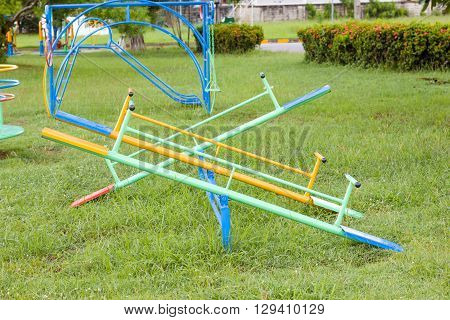 Empty seesaw in a playground on green grass