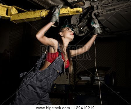 Beautiful young female mechanic inspecting car in auto repair shop. Sexy mechanic.