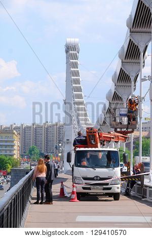 Moscow, Russia - May, 6, 2016: workers on the car lift repair to elektrset on Krymsky Bridge in Moscow, Russia