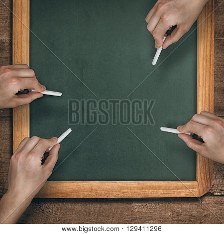 Multiple hands writing with chalk against chalkboard