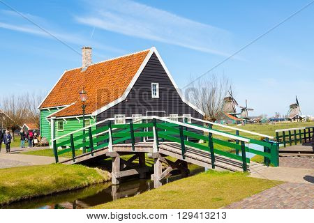 Zaanse schans, Netherlands - April 1, 2016: Zaanse Schans, North Holland, traditional village, tourists, green houses and windmills against blue cloudy sky