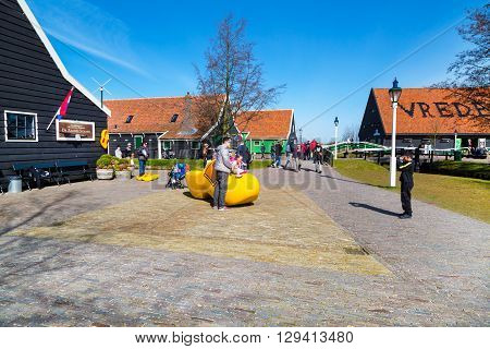 Zaanse schans, Netherlands - April 1, 2016:  People taking photos near big wooden shoe, clog or klomp, Zaanse Schans village, Holland