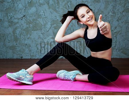 beautiful smiling teenage girl wearing sports clothes with a yoga mat and with her thumb up