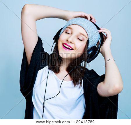 happy teenage girl with earphones listening to the music