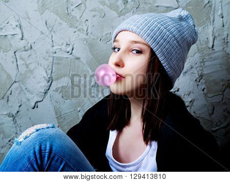 teenage girl with a bubble gum against old wall