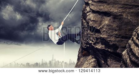Businessman pulling rope while sitting on cube against city on the horizon