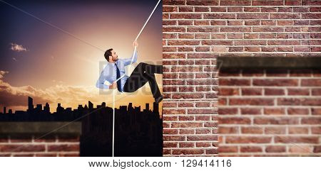Businessman pulling a rope with effort against red brick wall