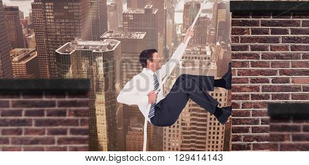 Businessman pulling a rope against red brick wall