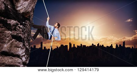 Businessman pulling a rope with effort against picture of city by sunrise
