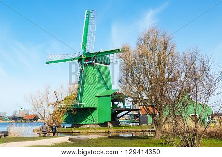 Zaanse schans, Netherlands - April 1, 2016: Green windmill in Zaanse Schans, North Holland, traditional village, tourists, blue sky