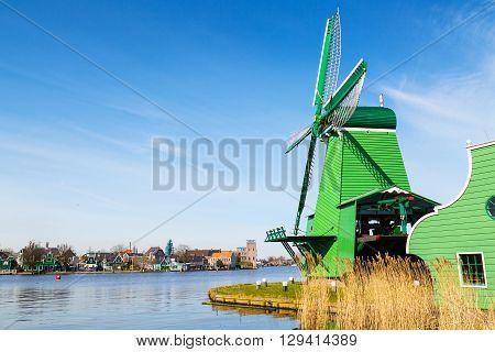 Green windmill in Zaanse Schans, North Holland, traditional village, tourists, blue sky