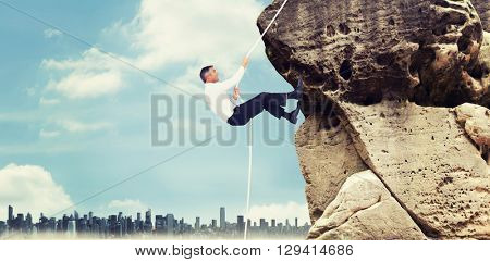 Businessman pulling rope while sitting on cube against large city on the horizon