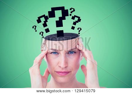 Pretty blonde suffering from headache looking at camera against green background