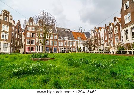 Colorful view of Begijnhof courtyard with historic Holland houses in Amsterdam, Netherlands