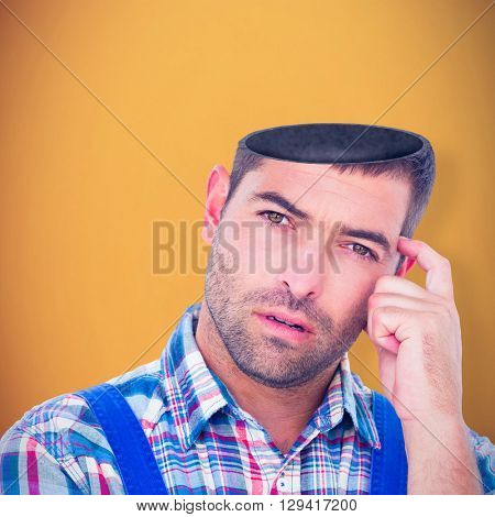 Portrait of confused manual worker scratching head against orange background