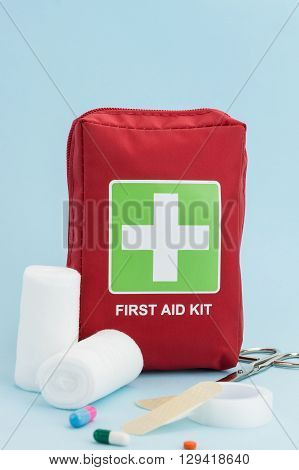 First Aid Kit With Medical Equipment, On Light Blue Background