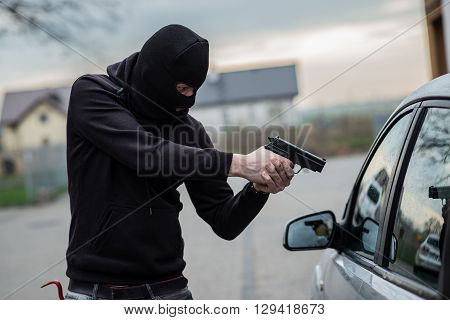 Car Thief Pointing A Gun At The Driver