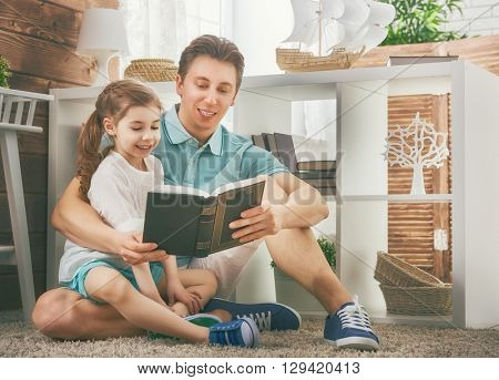 Happy loving family and Father's Day. Father reading a book to his daughter.