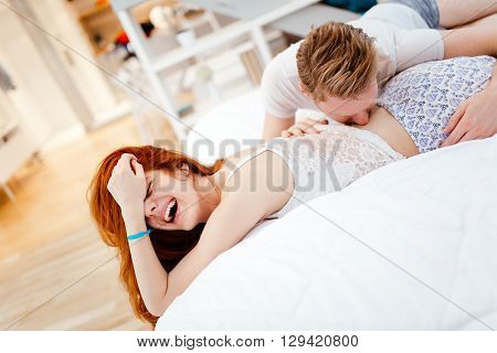 Heterosexual couple's foreplay in bed at beautiful setting
