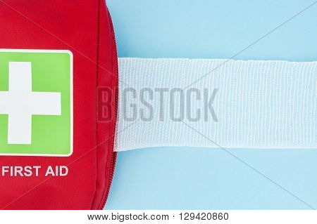 Red first aid kit with unrolled gauze on light blue background.