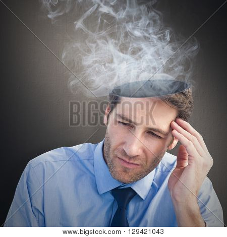 Stressed businessman holding his head against digital image of gray wall