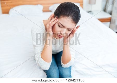 Woman sitting on the bed and having head pain at home