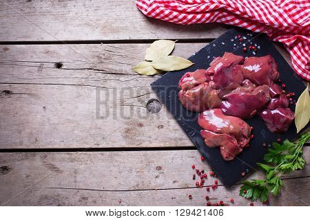 Raw chicken liver on slate board with towel on aged wooden background. Garnished with herb parsley and red pepper. Food ingredient. Selective focus. Place for text.
