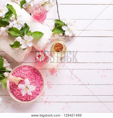 Spa or wellness setting. Pink sea salt in bowl bottles with aroma oil towels and flowers on white wooden background. Selective focus. Place for text. Square image.