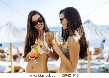 Beautiful young women sipping cocktails on beach