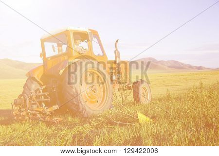 Mongolian farmer driving his tractor on the field.