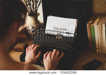 The word top secret against young woman using typewriter