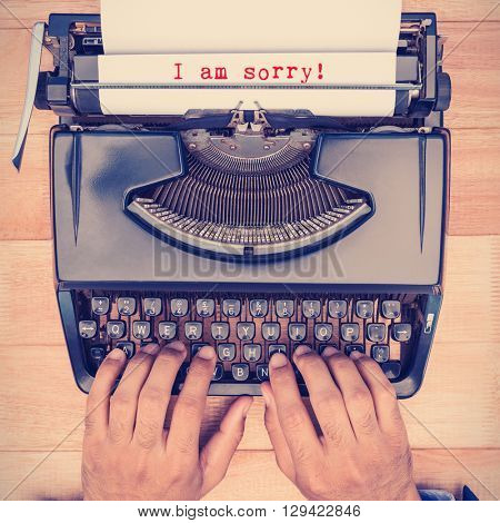 The sentence I am sorry against white background against businessman typing on typewriter