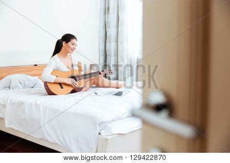 Happy woman playing records on guitar supported by laptop computer on the bed at home