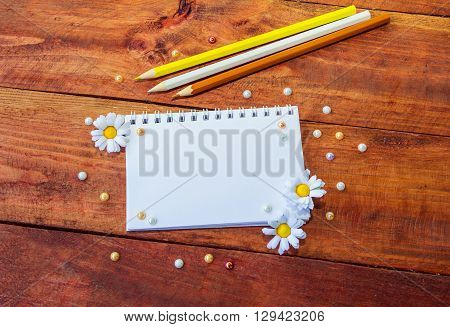 Blank notepad decorated by artificial chamomiles, yellow, white and brown pencils and colorful pearl beads on wooden background