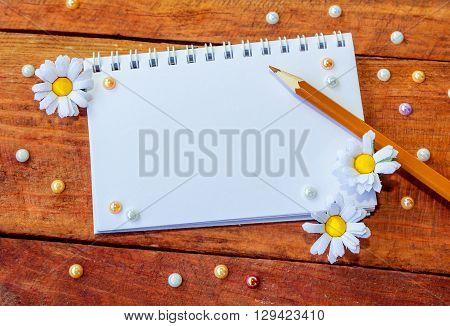 Blank notepad decorated by artificial chamomiles, brown pencil and colorful pearl beads on wooden background