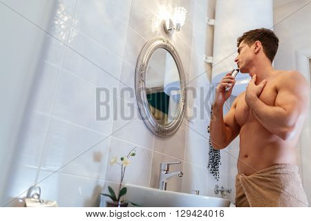 Handsome man shaving in bathroom reflection in mirror