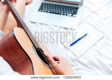 Cropped image of a female hands playing on guitar