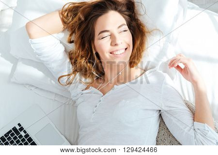 Happy woman lying on the bed and waking up in the morning