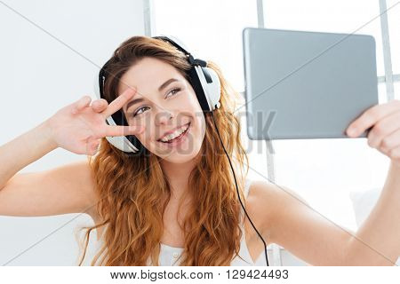 Happy woman in headphones making selfie photo on tablet computer at home