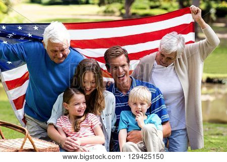 Multi-generation family holding american flag in the park on a sunny day