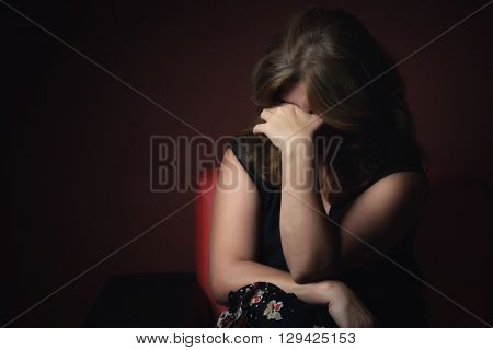 Portrait of a crying sad and depressed woman with a dark background