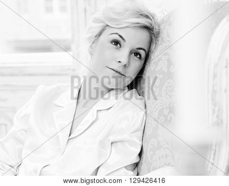 Black and white photo of daydreaming young woman.