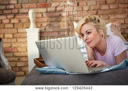 Young blonde woman lying on bed, using laptop computer, smiling.