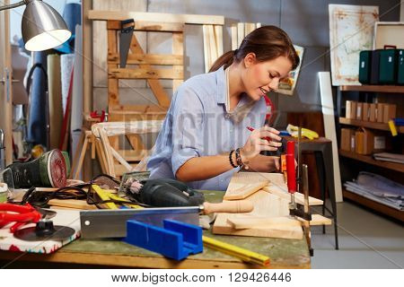 Attractive woman tinkering in home workshop.